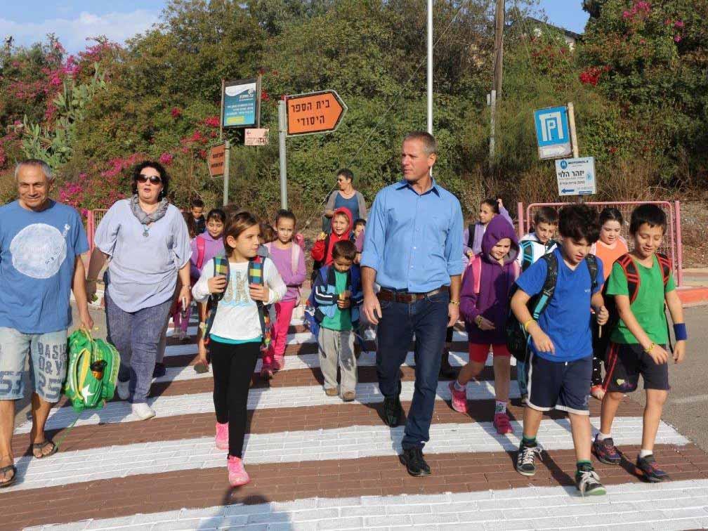 ראש המועצה נור צועד בבטחה במעבר חצייה עם תלמידי עמ