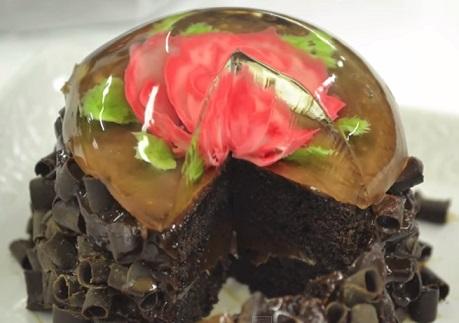פרח שושנה אדומה בתוך ג'לי על עוגת שוקולד