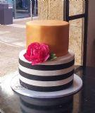 עוגת קומותיים בסגנון מודרני: פסים בשחור לבן, רקע זהב ופרח פיאוני ענק בצבע פוקסיה.