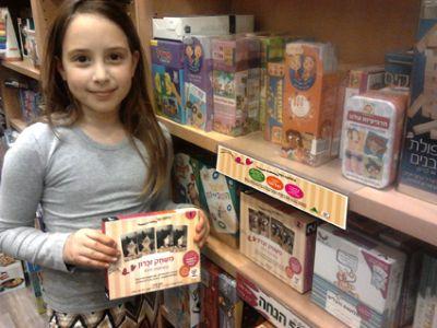 ילדה מראה אריזת משחק קלפים טיפוליים