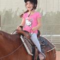 ילדה רוכבת על סוס רכיבה טיפולית