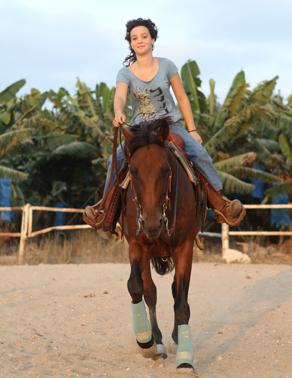 נערה רוכבת על סוס בחווה
