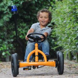ילד רוכב על מכונית פדלים באדי כתומה