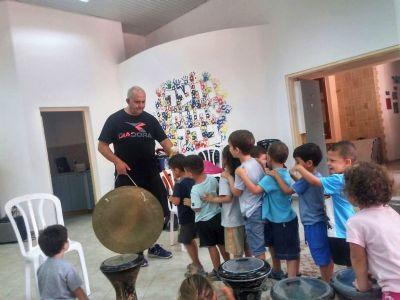 הילדים מתנסים בנגינה בכלי הקשה - גונג גדול.