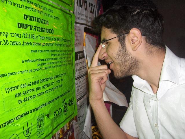 בחור ישיבה קורא מודעת פרסום בלוח מודעות